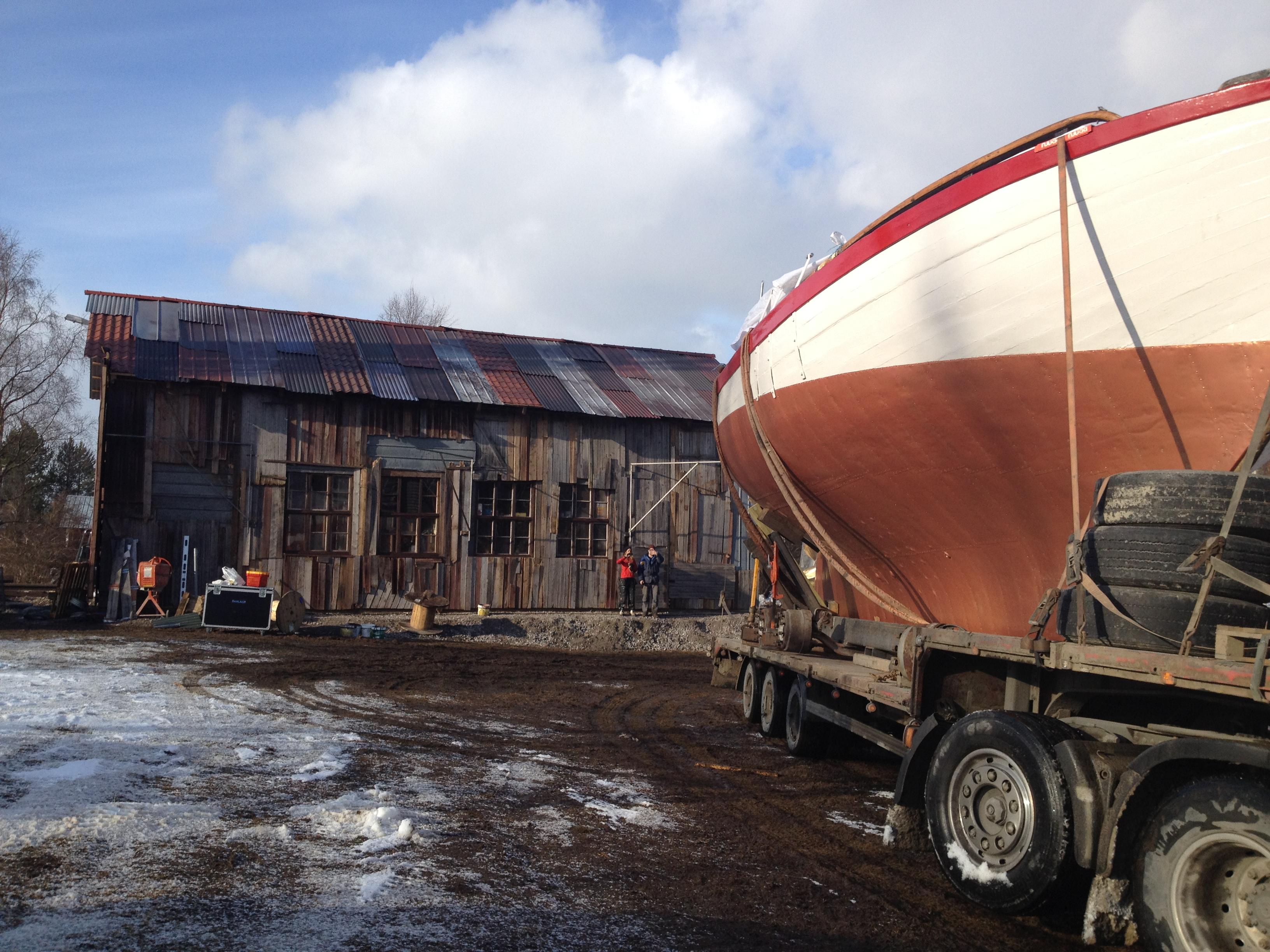 den enorma båten transporteras in i ladan som vi byggde på en åker